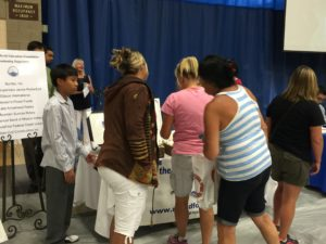 Teachers line up to purchase Nathan's art work at the 2016 Back to School Breakfast