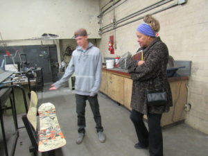 Student, Chase Rigney show Josita Todd a bench made from used snow boards in the welding shop